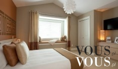 Przestronna sypialnia z dużym łóżkiem w jasnej kolorystyce.
