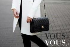 Biały klasyczny płaszcz i czarna pikowana torebka Chanel na ramię.