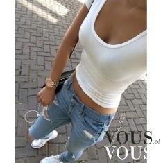Luźny styl. Krótki biały top i dżinsy z przetarciami. Jasne dżinsy i tenisówki.