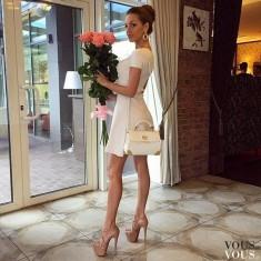 Urocza biała sukienka i szpilki.