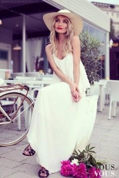 Biała maksi sukienka z kapeluszem. Obok kwiaty i rower, całość prezentuje się bardzo dziewczęco  ...