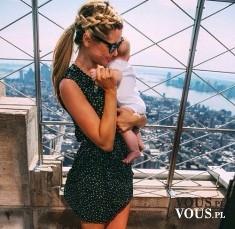 Dziewczyna z dzieckiem na rękach, w tle panorama miasta
