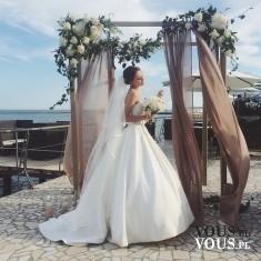 Piękna suknia ślubna z trenem i długim welonem. Romantyczna sceneria ślubna