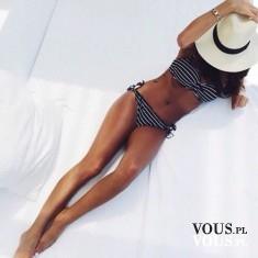 Kobieta o smukłej sylwetce w czarno-białym bikini w paski.