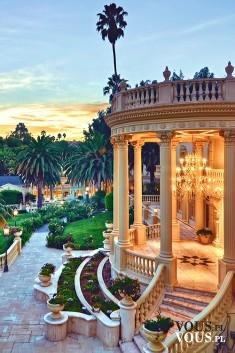 Piękny oświetlony taras. Duży ogród z palmami.