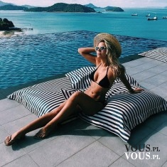 Opalanie nad brzegiem morza. Wakacyjny odpoczynek. Kobieta w czarnym bikini.