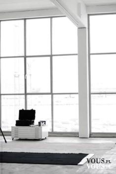 Białe minimalistyczne wnętrze z dużą przestrzenią i dużymi oknami na całych ścianach.