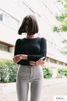 Spodnie w biało-czarną kratkę i czarny sweter. Krótkie włosy.