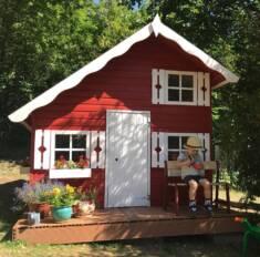 Drewniany domek ze spadzistym dachem i małym pięterkiem pomalowany na czerwono z białymi okienni ...