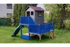 Drewniany domek dla dzieci zbudowany na dwupoziomowej platformie, pomalowany na mocne ale spokoj ...