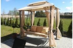 Ozdobna metalowa huśtawka ogrodowa z beżowym, materiałowym dachem. Delikatne moskitiery pozwolą  ...