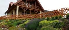 Płot myśliwski otaczający teren z domem w stylu góralskim. Konstrukcja płotu idealnie komponuje  ...