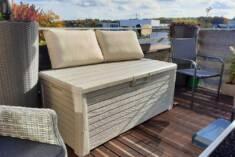 Skrzynia balkonowa w kolorze beżowym pełni podwójną funkcję. Jest zarówno wygodnym siedziskiem j ...