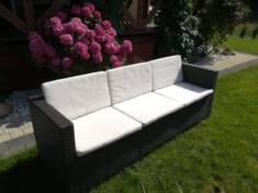 Wygodna 3-osobowa sofa ogrodowa została ustawiona na trawniku w słonecznej części ogrodu. Siedzą ...
