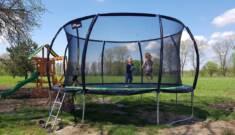 Duża trampolina ogrodowa z bawiącymi się dziećmi na tle zielonego pola. Wewnętrzna siatka oraz o ...
