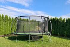 Wyjątkowo duża trampolina ogrodowa ustawiona w zielonym kącie ogrodu. Dzięki siatce bezpieczeńst ...