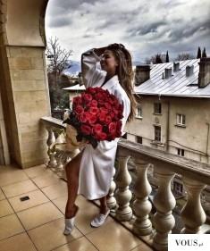 Kobieta z bukietem róż w białym szlafroku na balkonie