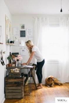 Kobieta przy biurku, blond włosy, parkiet drewniany, stylowe półki wykonane z drewnianych skrzyń ...
