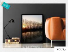 Fotografia w formie plakatu w ramie z motywem drzew odbijających się w wodzie na tle zachodząceg ...