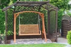 Niezwykle elegancka drewniana huśtawka ogrodowa postawiona pod drewniana pergolą, która będzie s ...