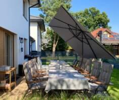 Rozkładany parasol ogrodowy ustawiony nad długim stołem jadalnym w ogrodzie. Dzięki dużej czaszy ...