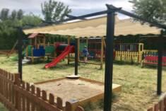 Metalowa pergola ogrodowa ustawiona nad piaskownicą na osiedlowym placu zabaw. Dzięki rozsuwanej ...
