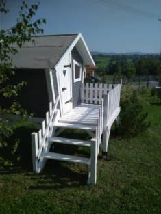 Piękny domek dla dzieci w stonowanych, biało-szarych barwach zbudowany na lekkim wzniesieniu. Z  ...