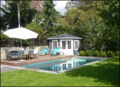 Drewniany domek Belgia postawiony w rogu ogrodu z basenem idealnie spełnia funkcję przebieralni. ...