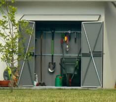 Prosty metalowy domek narzędziowy postawiony przy ścianie budynku mieszkalnego. Dzięki dwuskrzyd ...
