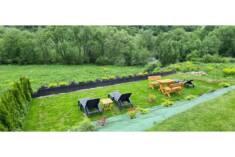 Wygodne leżaki ogrodowe ustawione zostały w ogrodzie z pięknym widokiem na las i zieloną łąkę. D ...