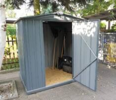 Metalowy domek ogrodowy z podłogą z płyty wiórowej ustawiony na podłożu z kostki brukowej. Domek ...