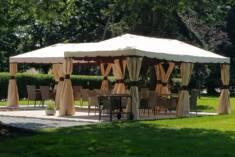 Dwa kremowe pawilony ustawione w dużym ogrodzie osłaniają wygodne stoliki i krzesła. Pawilony og ...