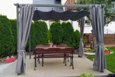 Metalowa pergola tarasowa osłania stół o ławki przed promieniami słońca. Pergola jest wyposażona ...