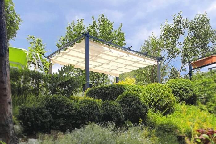 Metalowa pergola trasowa z rozkładanym  materiałowym dachem ustawiona w bujnym ogrodzie. Lekka k ...
