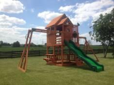 Duży drewniany plac zabaw ustawiony w ogrodzie na pięknym i wyjątkowo równym trawniku.  Na tle p ...