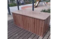 Duża solidna skrzynia ogrodowa ustawiona w pobliżu placu zabaw. Skrzynia jest wykonana z metalow ...
