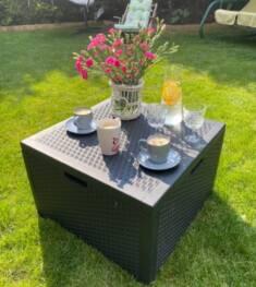 Nieduży ale bardzo wygodny stolik kawowy na planie kwadratu został ustawiony na trawniku w ogrod ...