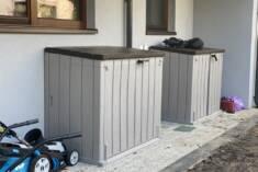 Dwie szare szafy ogrodowe z plastiku imitującego drewno. Szafy mogą być zamykane na kłódkę, dzię ...