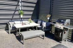 Nowoczesny zestaw mebli tarasowych z aluminium złożony z narożnika, stolika oraz niskiej ławki.  ...