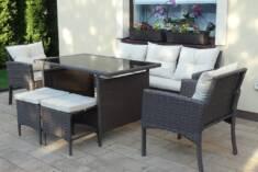 Klasyczny zestaw mebli ogrodowych z technorattanu, składający się z dwóch foteli, sofy, stołu i  ...